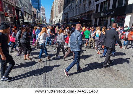 NEW YORK CITY - OCTOBER 06, 2015: crowds of people crossing a street in midtown Manhattan. The metropolitan area NYC is one of the most important economy areas and commercial center of the world - stock photo