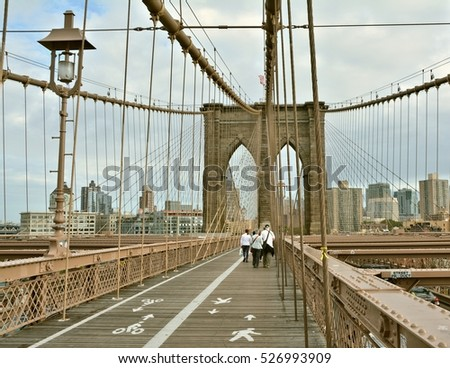 NEW YORK CITY - OCTOBER 15, 2014: People walk on Brooklyn Bridge. Brooklyn Bridge connects boroughs of Manhattan and Brooklyn over East River
