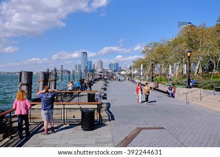 NEW YORK CITY - OCTOBER 8, 2014: People walking the boardwalk of Battery Park a windy october day on Manhattan - stock photo