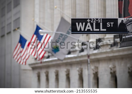 NEW YORK CITY - OCTOBER 13: Wall Street Sign on October 13, 2013 in New York, NY. Wall Street sign with USA flag and New York Stock Exchange at the background - stock photo