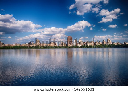 New York City - Panoramic view of modern buildings from Central Park with Jacqueline Kennedy Onassis Reservoir.