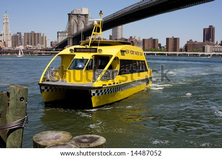 New York City's water taxi arriving at Fulton Ferry landing in Brooklyn. Here seen with the Brooklyn Bridge in the background on a bright sunny day with a depp blue sky. - stock photo