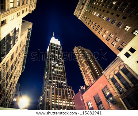 NEW YORK CITY - SEPT 13: Landmark Empire State and surrounding buildings in midtown Manhattan on night of Sept. 13, 2012. Completed in 1031, this historic skyscraper is 102 stories high. - stock photo