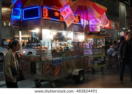 New York City - September 2016:  A hot dog stand vendor stays open late into the night to sell food to late night tourists. American snacks and traditional halal cuisine. Often called street meat.