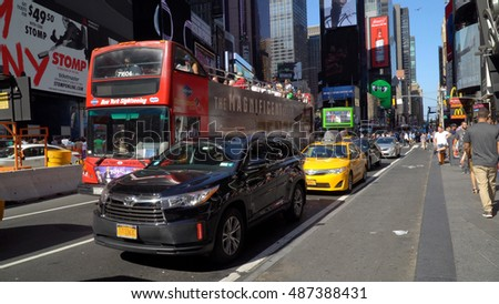 New York City - September 2016: Busy taxi, uber, and tour bus traffic travels through times square in midtown Manhattan. Large intersection with many cars and tourists - safety concerns NYPD protect