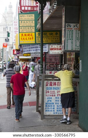 New York City, 11 september 2015: people and signs on the street in colorful chinatown manhattan new york city - stock photo