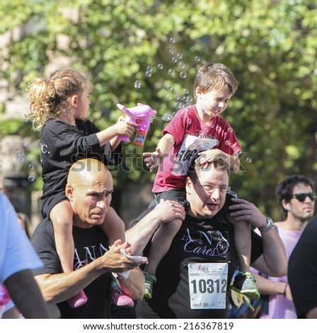 NEW YORK CITY - SEPTEMBER 7 2014: the Susan G Komen Race for the Cure took place along Central Park West with participants raising funds for breast cancer. Kids play bubbles on their dads' shoulders - stock photo