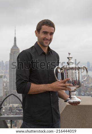 NEW YORK CITY - SEPTEMBER 9: US Open 2014 champion Marin Cilic posing with US Open trophy on the Top of the Rock Observation Deck at Rockefeller Center on September 9, 2014 in New York - stock photo