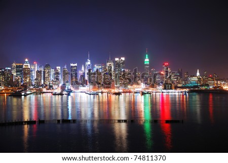 New York City Skyline at night with Times Square and Empire State Building with colorful reflections. - stock photo