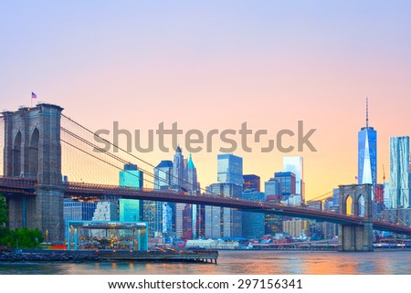 New York City skyline, Manhattan downtown panorama with famous landmark Brooklyn Bridge at colorful sunset - stock photo