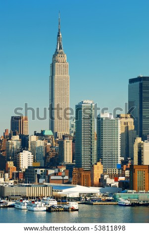 New York City skyline over Hudson river with boat and skyscraper with empire state building. - stock photo
