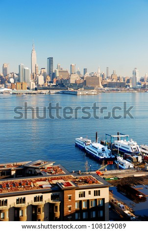 New York City skyline panorama over Hudson river with boat and skyscraper viewed from New Jersey. - stock photo