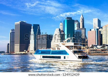 New York City skyline viewed from the water with a harbor boat in the foreground - stock photo