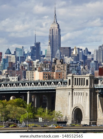 New York city skyline with focus on Empire State Building over the Manhattan Bridge using high contrast color