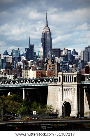 New York city skyline with focus on Empire State Building over the Manhattan Bridge using high contrast color - stock photo