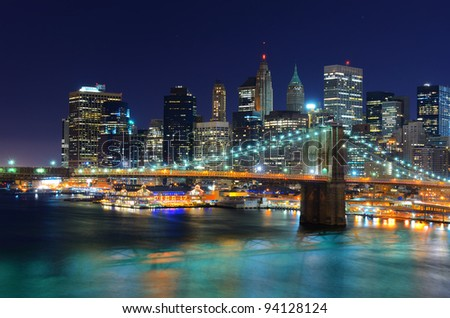 New York City skyline with the Financial District of Manhattan behind the Brooklyn Bridge at night.