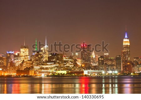New York City, USA colorful night skyline panorama with illuminated landmark buildings in downtown Manhattan business and residential districts