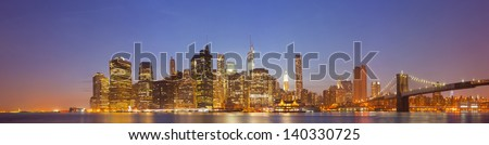 New York City, USA colorful night skyline panorama with illuminated landmark buildings in downtown Manhattan business and residential districts and famous Brooklyn Bridge - stock photo