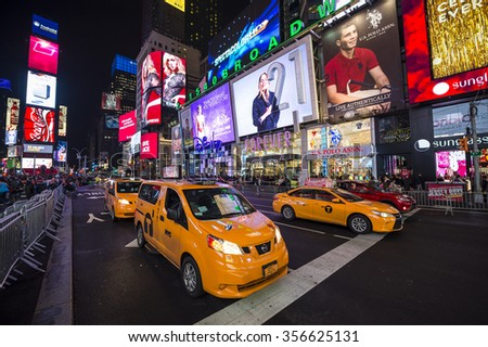 NEW YORK CITY, USA - DECEMBER 22, 2015: Yellow New York taxis pass crowds gathering under the bright lights of Times Square in the build-up to New Year's Eve. - stock photo