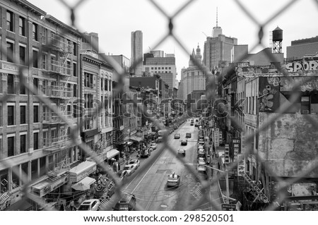 NEW YORK CITY, USA - JULY 03, 2015: Downtown Manhattan and Chinatown viewed through a chainlink fence on the Manhattan Bridge. - stock photo