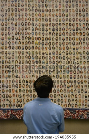 NEW YORK CITY, USA - May 17, 2014: Man looking at photos of victims of the terrorist attacks at the Twin Towers at the National 9/11 Memorial Museum at Ground Zero in Lower Manhattan.  - stock photo