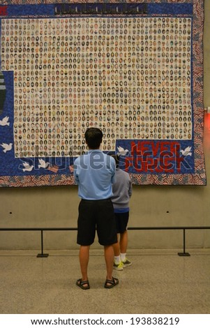 NEW YORK CITY, USA - May 17, 2014: People looking at a quilt in the National 9/11 Memorial Museum at Ground Zero in Lower Manhattan.  - stock photo