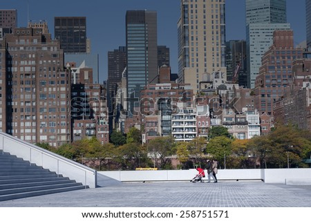 NEW YORK CITY, USA - OCTOBER 25: Parents walk at Roosevelt Island Four Freedoms Park, in the background is Manhattan East Midtown skyline at sunrise on October 25, 2013. in New York City - stock photo