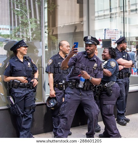 NEW YORK CITY / USA - 2015-06-14  Police officers prepared for the 57th annual Puerto Rican Day Parade.  Morale seemed high as an unidentified jubilant officer snapped a selfie with his comrades.