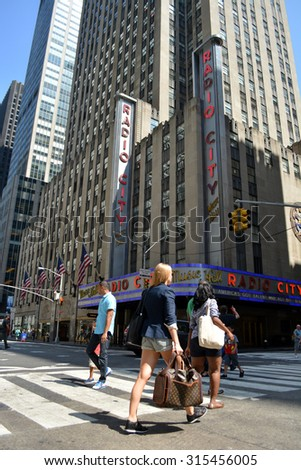 New York City, USA - September 7, 2015: People crossing Sixth Avenue in front of Radio City Music Hall in midtown Manhattan in New York City. - stock photo
