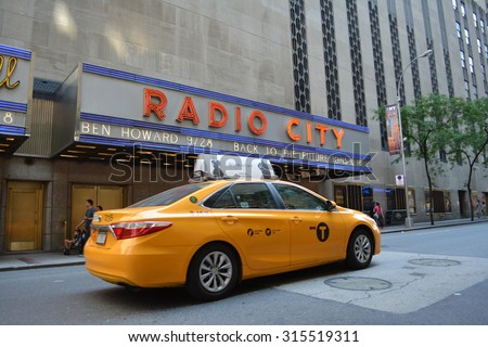 New York City, USA - September 7, 2015: Taxi cab passing in front of Radio City Music Hall in midtown Manhattan in New York City.