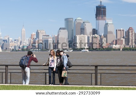 NEW YORK CITY, USA - SEPTEMBER 16, 2011: Tourists at Liberty Island take photos in front of the Lower Manhattan city skyline.