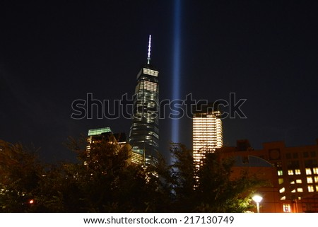 New York City, USA - September 11, 2014: World Trade Center Tower One and the Tribute in Light marking the anniversary of the terrorist attacks at Ground Zero in New York City.  - stock photo
