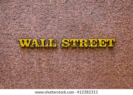 New York City Wall Street gold road sign in downtown Manhattan on the wall. Entrance to an office building on Wall Street name, downtown, financial district in New York City, USA. - stock photo