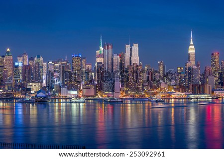 New York City with skyscrapers illuminated over Hudson River panorama