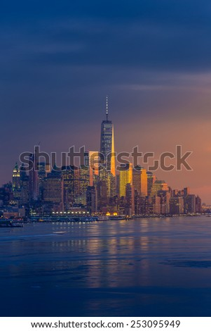 New York City with skyscrapers illuminated over Hudson River panorama, including the One World Trade Center - stock photo