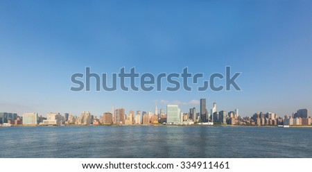 New York cityscape in the early morning. Photo taken from east looking at Manhattan on a sunny day. Many skyscrapers with river on foreground and plain sky above. - stock photo