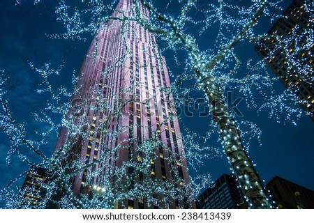 NEW YORK-DECEMBER 12: Looking up at the skyscraper and Christmas lights in Rockefeller Center during the holiday season on December 12, 2014 in Manhattan. - stock photo