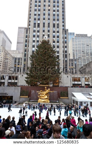 NEW YORK - DECEMBER 26: The Rockefeller Center Christmas Tree and statue of Prometheus above the ice rink on December 26 2012 in Manhattan New York. Rockefeller Center is a National Historic Landmark - stock photo