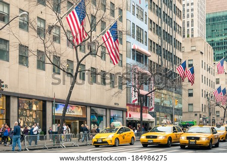 "NEW YORK - DECEMBER 22, 2013: yellow taxicabs and american flags on the 5th Avenue, named ""The most expensive street in the world"" at the crossroad with West 48th Street in Midtown Manhattan. - stock photo"
