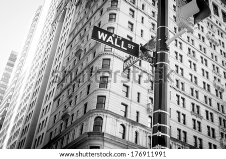 NEW YORK - FEB 10: Sign for Wall Street in New York City on February 10, 2014. Wall Street is the financial district of New York City, named after and centered on the eight-block-long, 0.7 miles long. - stock photo