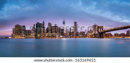 New York Financial District and the Lower Manhattan at dawn viewed from the Brooklyn Bridge Park. - stock photo