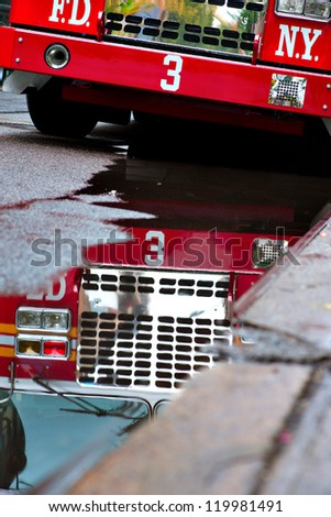 New York fire engine reflected in puddle in street - stock photo