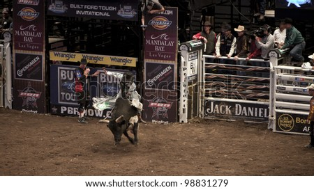 NEW YORK - JAN 10: A bull rider tried to stay on the bull for 8 seconds during the Professional Bull Rider tournament on January 10, 2009 in New York, NY. - stock photo