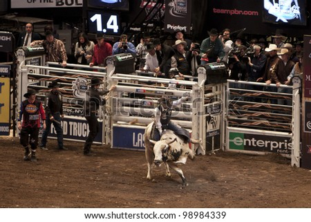 NEW YORK - JAN 10: An unidentified bull rider tried to stay on the bull for 8 seconds during the Professional Bull Rider tournament on January 10, 2009 in New York, NY. - stock photo