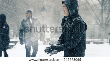NEW YORK - JAN 26, 2015: Asian man in blizzard wiping snow off gloves in Washington Square Park in Manhattan New York. The nor'easter snowstorm of 2015 was named Juno. - stock photo