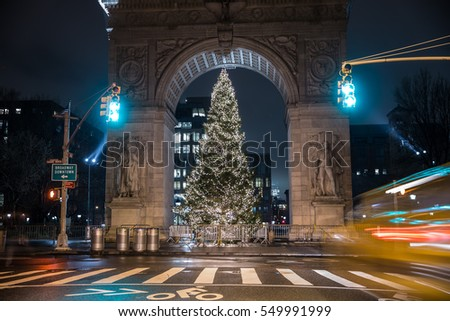 NEW YORK - JAN 3, 2017: green traffic lights and blurred taxi, crosswalk at Washington Square Park with Christmas tree under famous arch at night in NYC. Lower 5th Ave ends at WSP North in Manhattan.