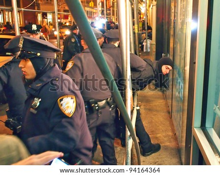 NEW YORK - JAN 29: Police detain a protester at an Occupy Wall Street march, January 29, 2012 in New York City. Demonstrators rallied to protest police action earlier that weekend at Occupy Oakland. - stock photo