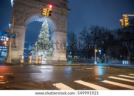 NEW YORK - JAN 3, 2017: quiet lonely crosswalk at night with Christmas tree under Washington Square Park arch in Manhattan. WSP is a public park in Greenwich Village in NYC.