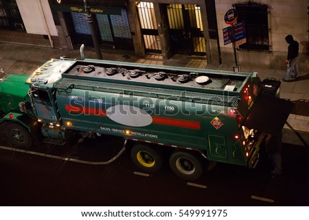 NEW YORK - JAN 3, 2017: sewage cesspool pump truck outside building on Manhattan street at night in NYC. Many businesses and residences use carting and sewage services after hours to avoid traffic.