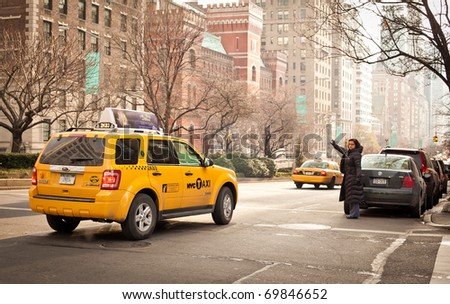 NEW YORK - JAN 6: Woman catches a taxi on Madison Avenue on January 6, 2011 in Manhattan, New York City - stock photo